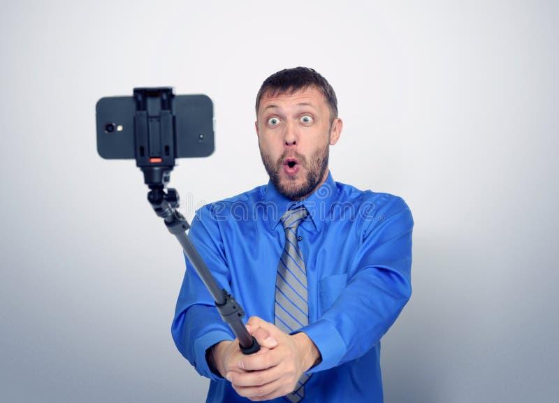 Lustiger bärtiger Mann in der Bindung, die selfie mit einem Stock macht lizenzfreie stockfotos