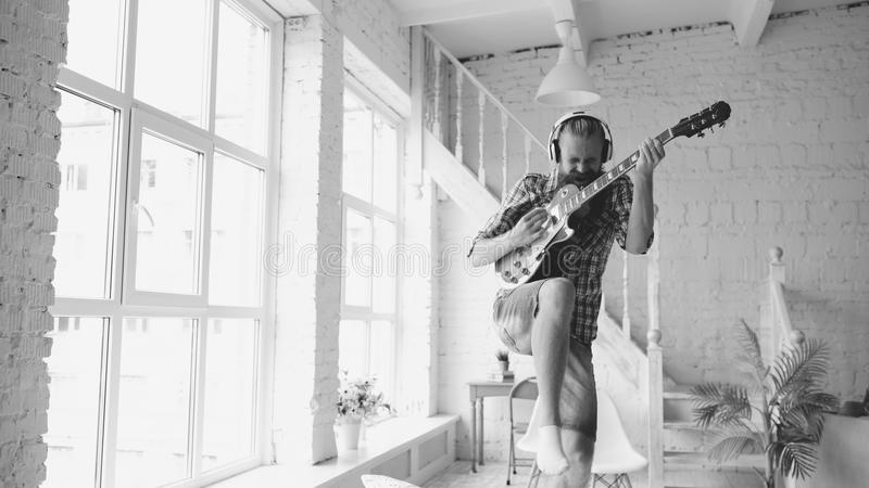 Lustiger bärtiger Manntanz auf dem Bett, das zu Hause E-Gitarre im Schlafzimmer singt und spielt stockfotografie