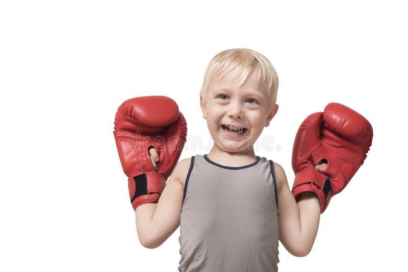 Lustiger blonder Junge in den roten Boxhandschuhen Sport-Konzept stockfoto