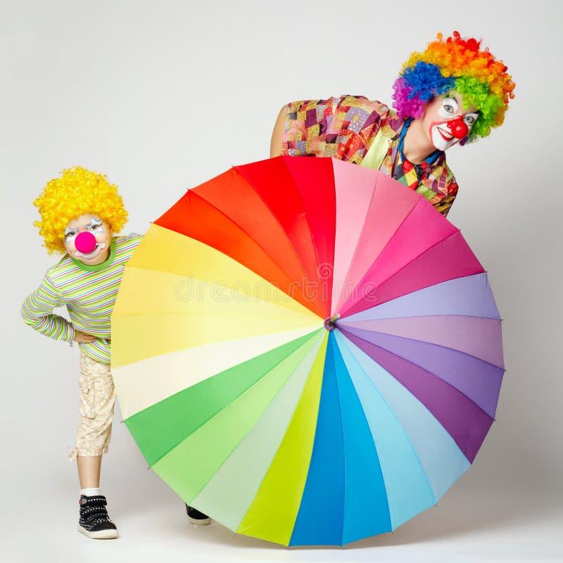 Lustiger Clown mit buntem Regenschirm stockfotos