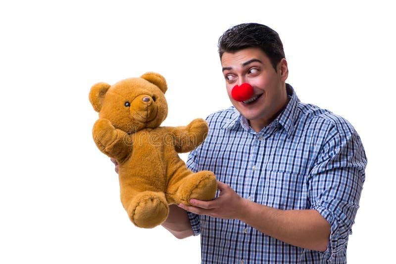 Lustiger Clownmann mit einem weichen Teddybärspielzeug lokalisiert auf weißem BAC lizenzfreies stockfoto