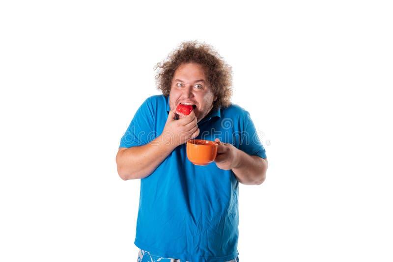 Lustiger dicker Mann mit Becher Kuchen essend Alles Gute zum Geburtstag lizenzfreie stockbilder
