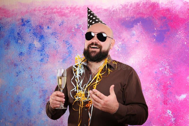 Lustiger dicker Mann mit Parteihut und Glas Champagner stockbild