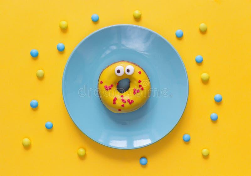 Lustiger Donut in der gelben Glasur mit Gesicht auf einer blauen Platte lizenzfreies stockfoto