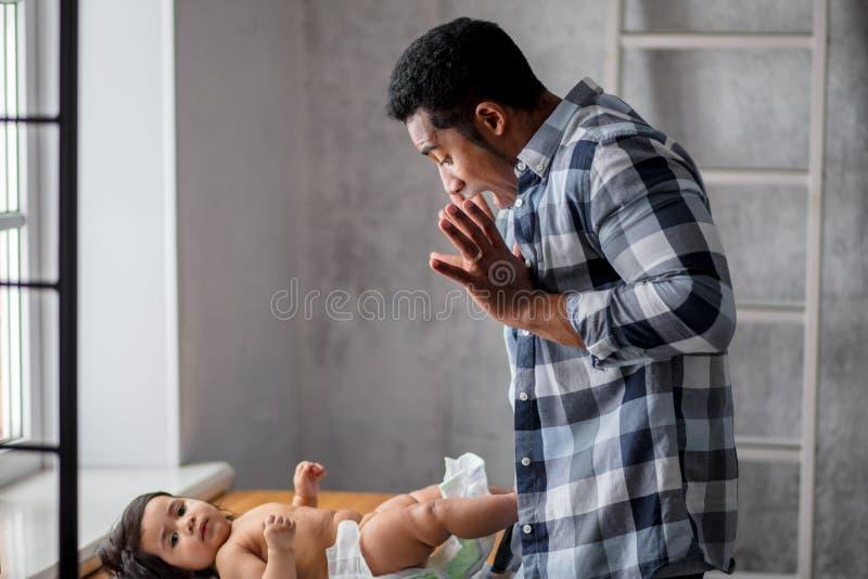 Lustiger emotionaler Mann, der Spaß mit seinem Baby hat lizenzfreie stockfotos