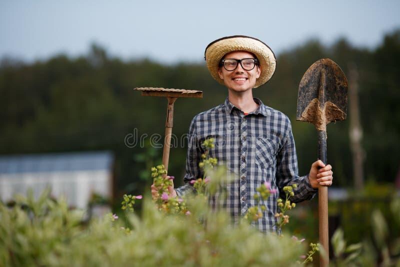 Lustiger Gärtner, der draußen eine Schaufel und eine Rührstange hält lizenzfreie stockfotos