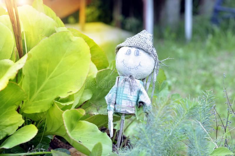 Lustiger Gartenzwerg, der unter netten Blumen steht lizenzfreie stockfotografie