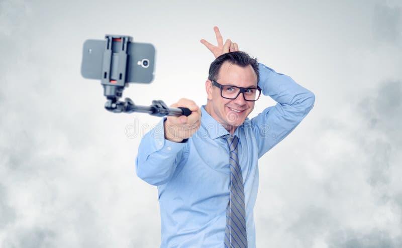 Lustiger Geschäftsmann in den Gläsern, die selfie mit einem Stock machen lizenzfreie stockfotos