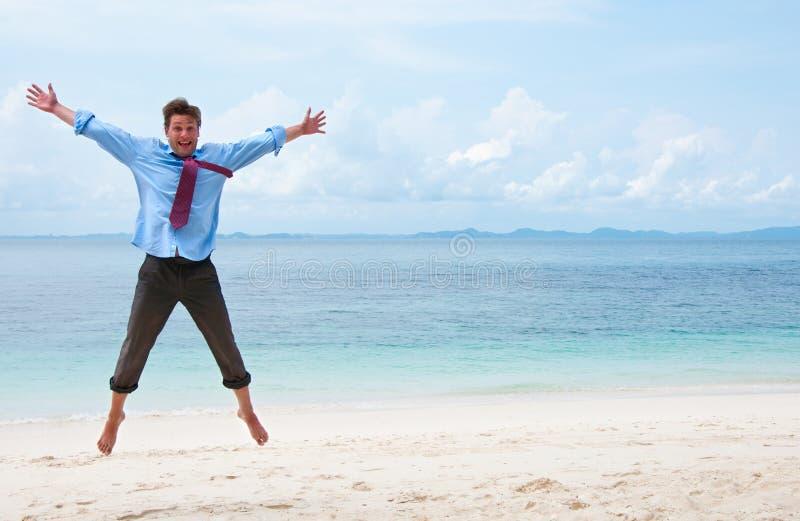 Lustiger Geschäftsmann, der auf den Strand springt lizenzfreies stockfoto