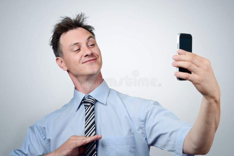 Lustiger Geschäftsmann, der auf einem Smartphone sich fotografiert lizenzfreie stockfotografie