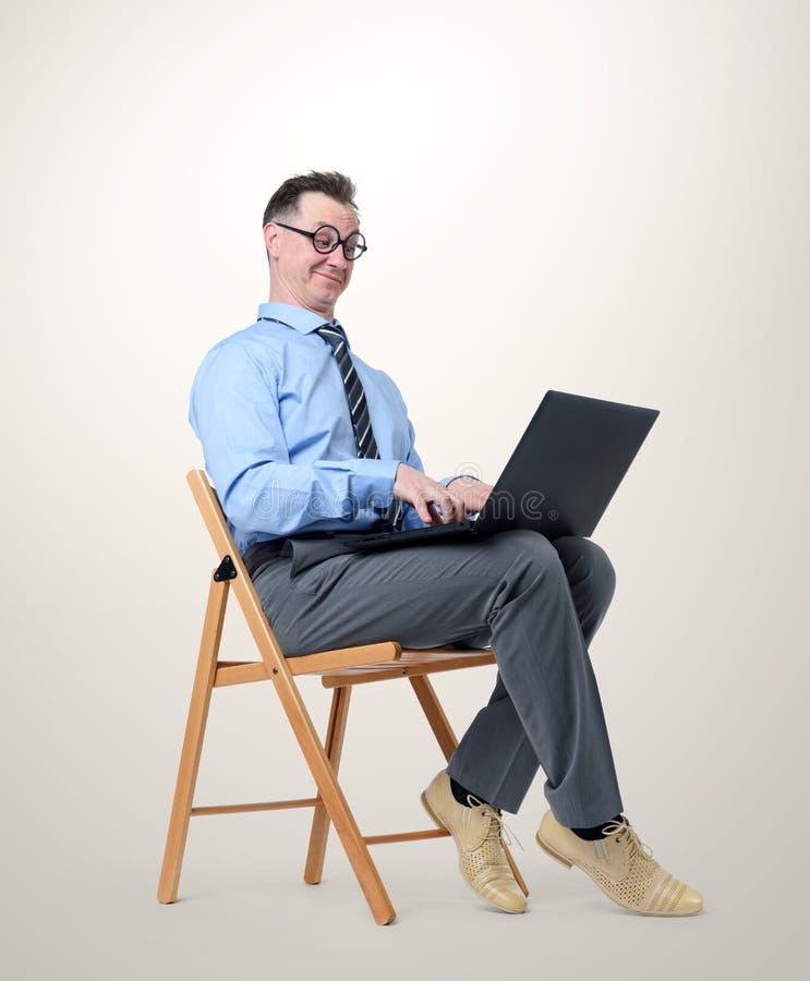 Lustiger Geschäftsmann mit einem Laptop, der in einem Stuhl auf Hintergrund sitzt lizenzfreie stockfotografie
