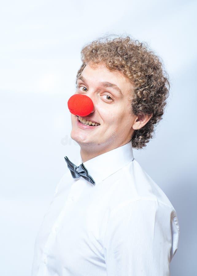Lustiger Geschäftsmann mit roter Clownnasenatelieraufnahme. lizenzfreies stockbild