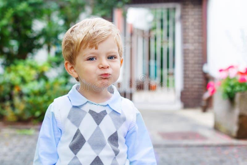 Lustiger glücklicher und lächelnder Kinderjunge auf Weise zur Kindertagesstätte stockfoto