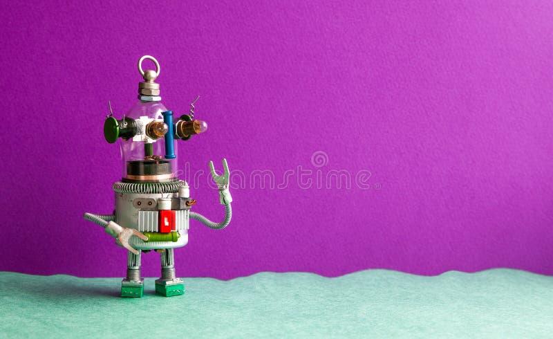 Lustiger Glaskopf-UFO-Roboter auf einem violetten grünen Hintergrund Humanoid Spielzeug des futuristischen Roboters mit der angeh lizenzfreie stockfotografie