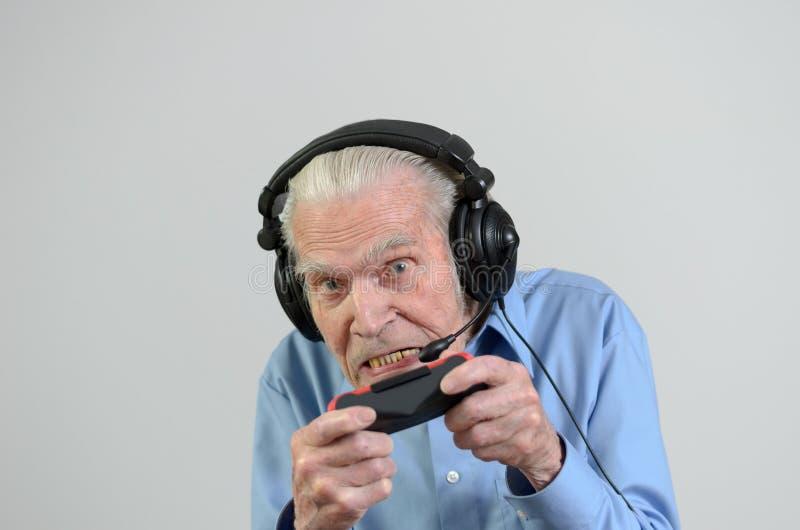 Lustiger Großvater, der ein Videospiel auf Konsole spielt lizenzfreie stockbilder
