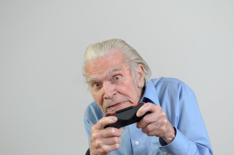 Lustiger Großvater, der ein Videospiel auf Konsole spielt stockfotografie