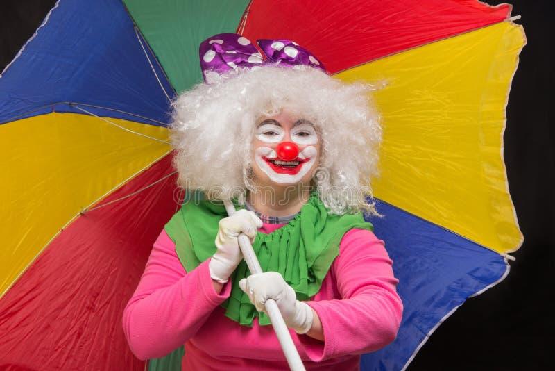 Lustiger guter lustiger Clown mit einem mehrfarbigen Regenschirm auf einem Schwarzen stockfotografie