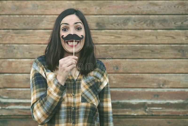 Lustiger Holdingschnurrbart der jungen Frau auf Stock stockfoto