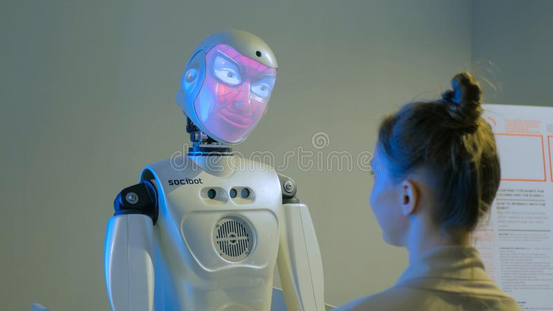 Lustiger Humanoidroboter mit der Auszeichnungsschrift, die mit Frau spricht stockbild