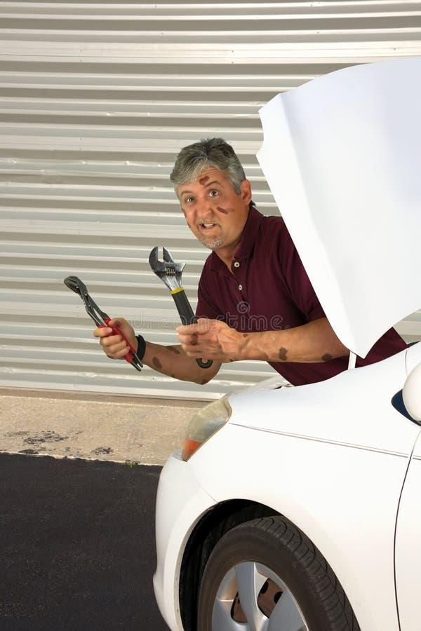 Lustiger humorvoller Mechaniker bedeckt im Fett mit verwirrtem Blick auf seinem Gesicht stockbilder