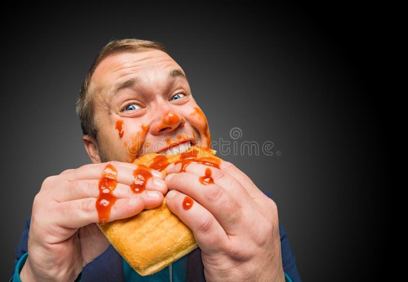 Lustiger hungriger dicker Mann schmutzig durch Ketschup stockbilder