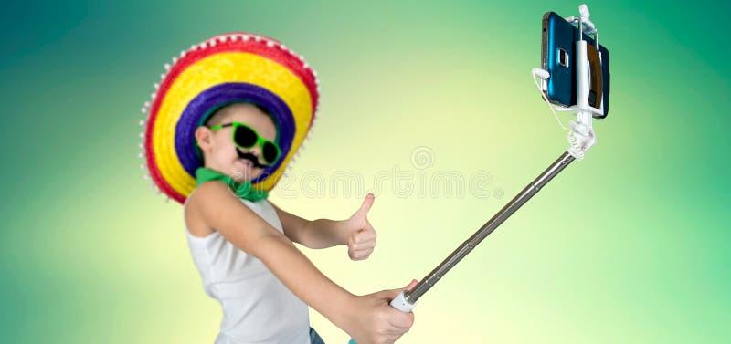 Lustiger Junge in der Sonnenbrille und im mexikanischen Sombrero macht ein Foto am Telefon lizenzfreies stockfoto