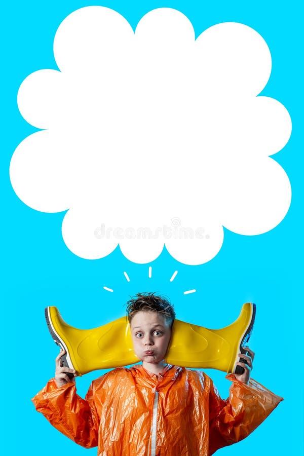 Lustiger Junge in einem orange Mantel mit luftgestoßenen-heraus Backen und Gummistiefeln auf blauem Hintergrund stockbilder