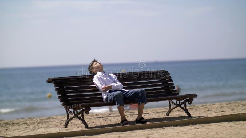 Lustiger Junge ist ermüdet und versuchend, auf einer Bank nahe dem Strand zu schlafen stockfoto