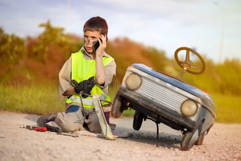 Lustiger Junge mit Autospielzeug nennend von der Handystraßenunterstützung stockfotografie