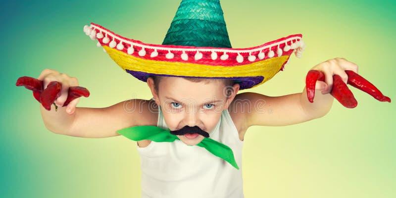 Lustiger Junge mit einem gefälschten Schnurrbart und in den mexikanischen Sombrerospielen stockfotografie