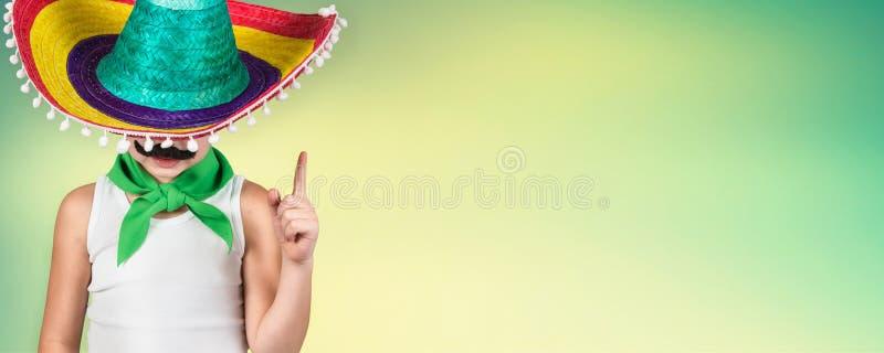 Lustiger Junge mit einem gefälschten Schnurrbart und im mexikanischen Sombrero lizenzfreies stockfoto