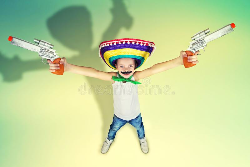Lustiger Junge mit einem gefälschten Schnurrbart und im mexikanischen Sombrero spielt mit Spielzeugpistolen stockfotografie