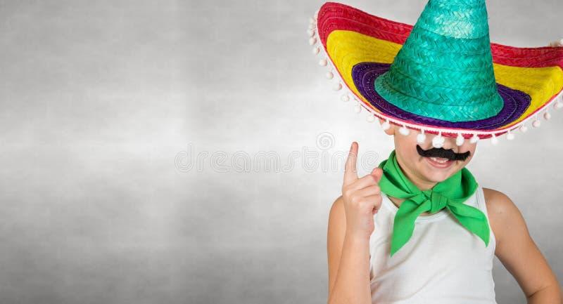 Lustiger Junge mit einem mexikanischen Sombrero des gefälschten Schnurrbartes stockfotografie