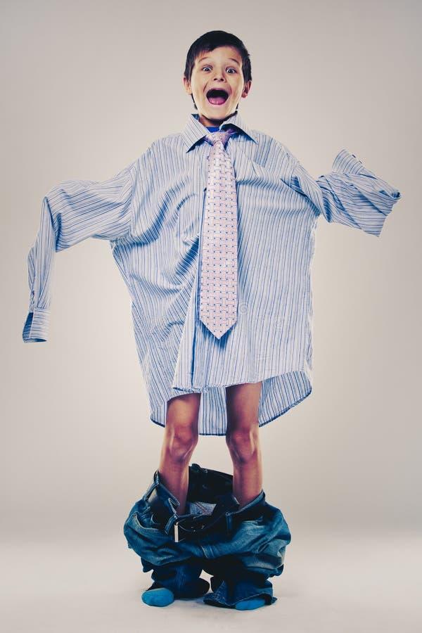 Lustiger Junge tragende Vati ` s Kleidung lizenzfreie stockbilder