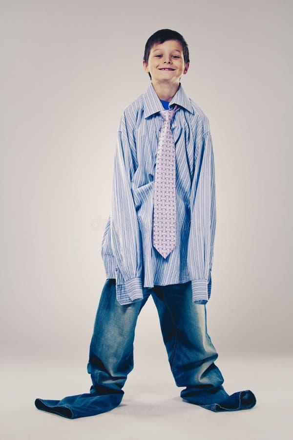 Lustiger Junge tragende Vati ` s Kleidung stockbild