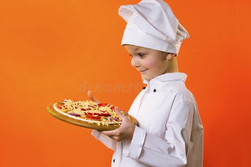 Lustiger Jungenchef kochte Pizza auf einem Brett lizenzfreie stockfotos