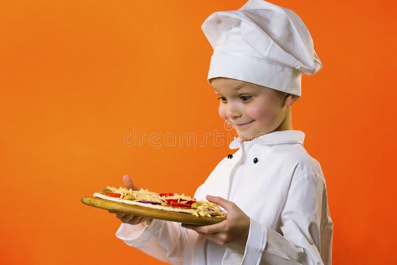 Lustiger Jungenchef kochte Pizza auf einem Brett lizenzfreies stockbild