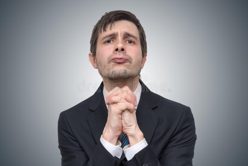 Lustiger junger Geschäftsmann ist, bitten bitten oder um Hilfe lizenzfreies stockfoto