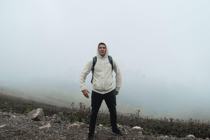Lustiger junger Mann in den Bergen, die herum, lustige Gesichter und Haltungen machend täuschen stockbild