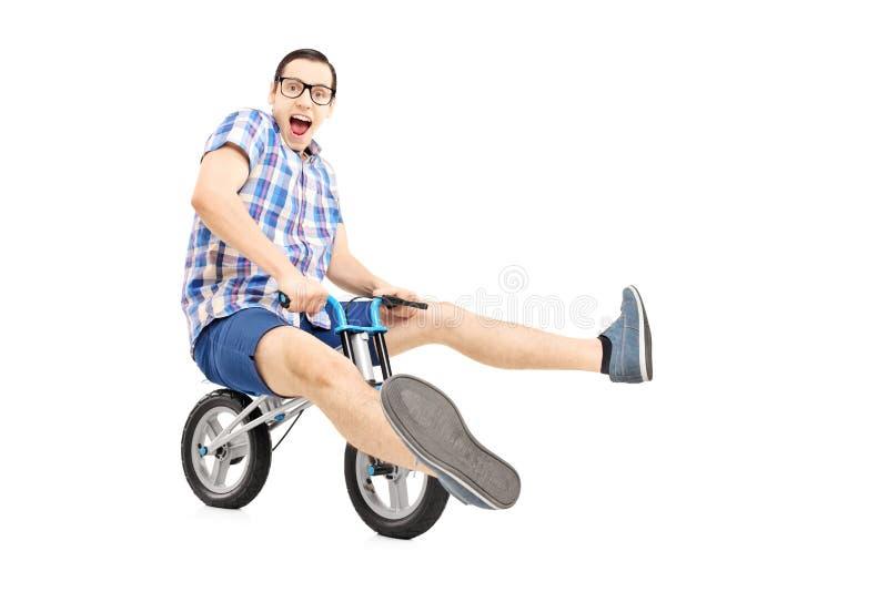 Lustiger junger Mann, der kleines Fahrrad fährt stockfotos