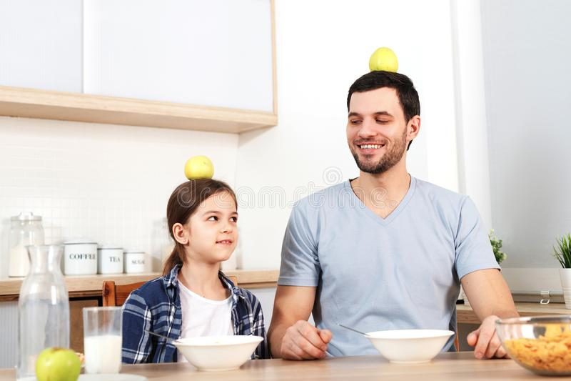 Lustiger junger Vati und Tochter sitzen neben einander, essen köstliche Corn-Flakes, halten Äpfel auf Kopf, demonstrieren das stockbild
