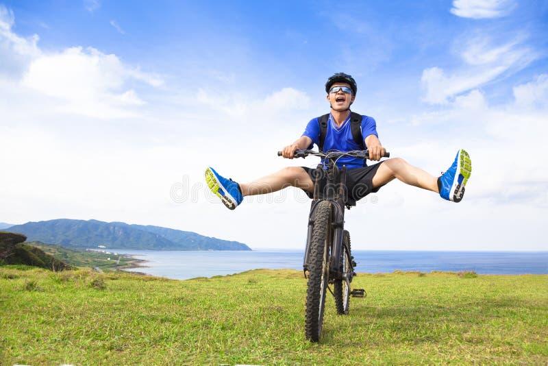 Lustiger junger Wanderer, der Fahrrad auf eine Wiese fährt lizenzfreie stockbilder