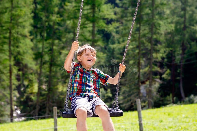 Lustiger Kinderjunge, der Spaß mit dem Kettenschwingen auf Spielplatz im Freien beim Sein nasses gespritzt mit Wasser hat Kind, d stockfotografie