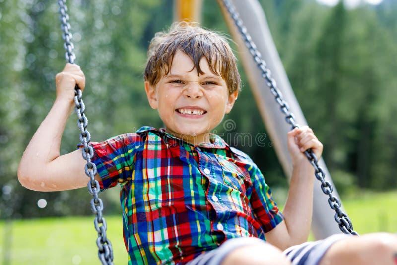 Lustiger Kinderjunge, der Spaß mit dem Kettenschwingen auf Spielplatz im Freien beim Sein nasses gespritzt mit Wasser hat Kind, d stockfoto