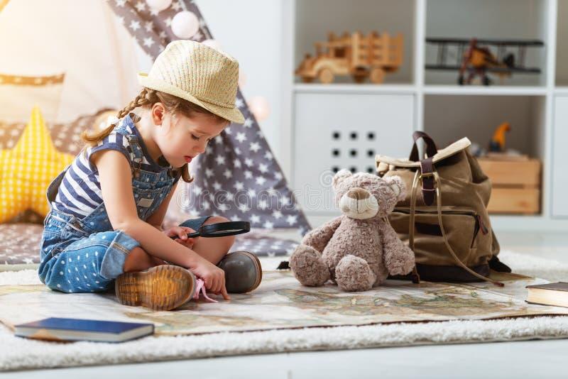 Lustiger Kindermädchentourist mit Weltkarte, Rucksack und Vergrößerungsglas lizenzfreie stockfotografie