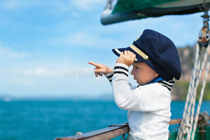 Lustiger kleiner Babykapitän an Bord von Segeljacht stockfoto