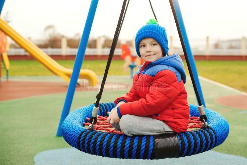 Lustiger kleiner Junge, der draußen am modernen Spielplatz schwingt Kleinkind, das im kühlen Wetter spielt Gesunde und glückliche lizenzfreie stockfotos