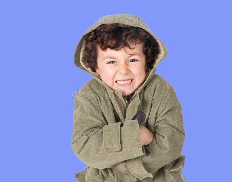 Lustiger kleiner Junge, der mit Kälte zittert lizenzfreies stockfoto