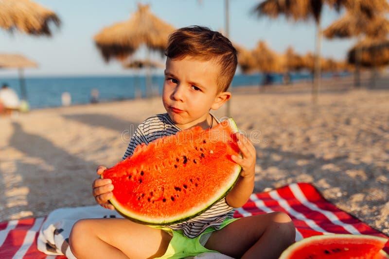 Lustiger kleiner Junge, der Wassermelone isst lizenzfreie stockfotografie
