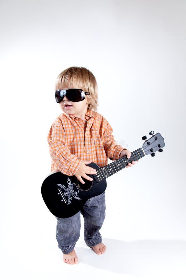 Lustiger kleiner Junge mit Ukulelegitarre stockfotografie